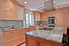 Aqua glass backsplash with maple cabinets.