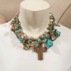 Multilayered cross necklace Multilayered charm and beaded cross necklace with turquoise and wood detailing never been worn no tags Jewelry Necklaces