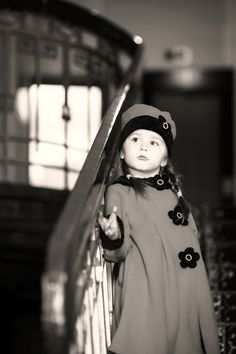 Cute little girl dressed in retro-style coat sitting on old staircase