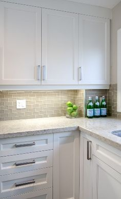 White shaker cabinets, gray glass subway tile backsplash, neutral quartz countertop