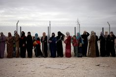"""""""Syrian refugee women stand in line to receive their families share of winter aid kits at Zaatari refugee camp, near the Syrian border, in Mafraq, Jordan, Dec. 3, 2013."""""""