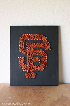 This San Francisco Giants String Art is entirely handmade. The wooden board is painted black and the SF Giants logo is strung with orange string