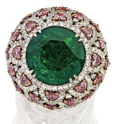 EMERALD, DIAMOND AND COLOURED DIAMOND RING Of bombé Design, centring a Round Brilliant cut Emerald weighing 7.29 carats within a Colourless Round Brilliant cut Diamond border above an openwork surround of heart shaped Pink tinted Diamonds and pavé set Colourless Round Brilliant cut Diamonds, to diamond set shoulders and pierced gallery, the Pink tinted and Colourless Diamonds together weighing approximately 1.50 carats and 3.20 carats respectively, mounted in platinum and 18c White Gold