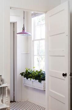 White-washed hallway with pastel pendant lighting and window foliage.