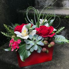Exclusive for Valentine's Day Our Love Note floral puts a romantic twist on our popular Texture Box floral arrangements by featuring red roses in a matching ceramic container. The roses are accented with red Sweet William, blackberries, cymbidium orchids,and three varieties of succulents before we finish them with greenery. Toppedn with a heart made of lily grass to make sure that Love Note delivers just the right message.