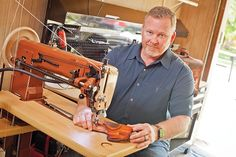 Curtis Sprague sews a gun holster in his garage workshop. He taught himself how to carve and stamp leather by watching YouTube videos.