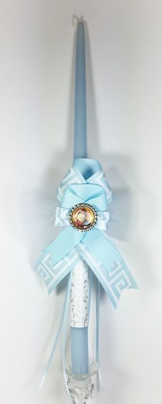 "An 18"" light blue candle is wrapped with silver sparkle print, Greek key ribbon with bottle cap icon.  ~WE CAN SHIP DIRECTLY TO YOUR GODCHILD~ Please provide shipping address during checkout. A gift notecard will be included. Leave your message in the NOTES section. Our candles are meticulously packaged with bubble wrap and paper to ensure the candles do not move during shipping. Variations to the ribbons, flowers, style and design may occur because they are seasonal and customized items."
