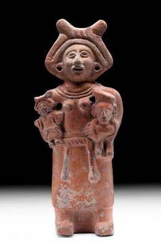 """Figurilla identificada como """"diosa madre""""; resalta la niña que carga, idéntica a ella en peinado, huipil, faja y enredo. Como parece ser también una sonaja y al mismo tiempo algunas similares contenían restos de niños, se piensa que pudieron haber tenido la función de juguetes que éstos utilizaron en vida.  Figura - Museo Nacional de Antropología"""