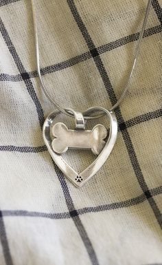 Our ribbon-like heart pendant is finished with a dog bone image in the center and a tiny paw print at the bottom, all crafted with recycled sterling silver. A shining expression of love for your dog, made in the U.S.A.