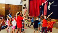 Harry Monster teaches kids superhero poses (along with Children's Librarian Kelsie Nygren) at Abilene Public Library's puppet show.