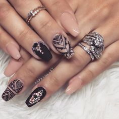 Stunning nude and black nails with nail art.