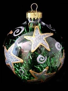 Hang this shimmering ornament on your Christmas tree and make a wish on it's many stars. These hand painted ornaments are adorned with gold stars filled with glittering centers. This design will inspire you to make all your wishes come true.