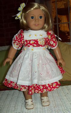 Fits 18 inch doll or American Girl Doll.   Doll dress, apron, and hair clip.Red daisy dress with eyelet apron.