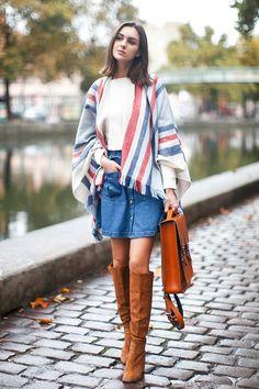 Foto de street style de como usar look com t-shirt branca, saia jeans de botões, poncho de listras, botas de camurça caramelo e bolsa carteiro
