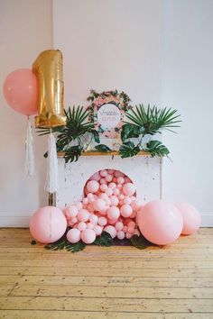 pink balloons falling from a faux fireplace