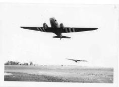 """A C47 transport pulls a british built """"Horsa"""" type glider loaded with american Airborne infantry into the air in the early morning of june 6,1944 = [Décollage d'un Douglas C-47 tractant un planeur Horsa]"""