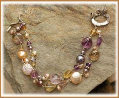 Champagne & Lavender IN THE MIX Ametrine, Freshwater Pearls, Citrine and Amethyst are hand-wrapped in sterling silver links. Dotted w/ small keish pearl charms and a beautifully handcrafted sterling toggle of carved Lilies...  SIZING IT UP Bracelet length is................7.25 fits a wrist size 6.0 to 6.50 perfect!