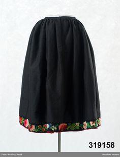Kjol av brunsvart halvylle i tuskaft med brunsvart linvarp (?) och inslag av tunt svart ullgarn. 5 våder, med rynkor i midjan mot  2 cm bred luinning av samma tyg, Sprund fram, knäppning med två hakar och hyskor. I kjolkanten påsytt 7 cm brett påsömsband av svart kläde med broderad blomranka i genomsydd plattsöm, stjälksöm, öppen kedjesöm, det som i Floda kalls påsöm, med ullgarn, Sefirgarn, i starka anilinfärger  i röda och rosa nyanser, klargrönt, gulgrönt, blått, anilinlila och vitt…