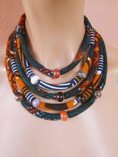 www.cewax.fr love this statement necklace ethno tendance, style ethnique, #Africanfashion, #ethnicjewelry - CéWax aussi fait des bijoux : http://www.alittlemarket.com/collier/fr_collier_plastron_multi_rang_ethnique_en_tissu_africain_beige_prune_jaune_-15921837.html -  Jai fait ce collier tribal africain orange et bleu relevé de tissus imprimés africains de cire et le résultat est superbe pièce ! Un collier de beauté