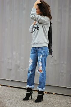 Black booties custom designed sweatshirt and custom distressed jeans cuffed at the him with cute accessories like a big bag, beanie and jewelry