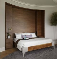 Morgante Wilson Architects built in a custom headboard with storage into this Master Bedroom.  Behind the walnut panels is storage.  A custom bed with linen wrapped legs sit in front.  The walls are painted Benjamin Moore Desert Light.