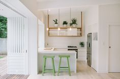In this minimal peninsula kitchen, I really like how the upper glass-fronted (or maybe plastic) cabinet is suspended from the ceiling. I like, too, how it is framed in wood. It's good that the fridge is built into that niche, so it doesn't stick out and draw too much attention.