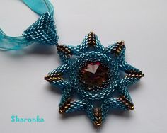 Osmicípá Osmicípá hvězda - obšitá rivoli Swarovski japonským rokajlem, zavěšená na saténové stužce. Velikost hvězdy je 6 cm.