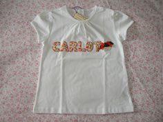 Camiseta personalizada a mano con el nombre de tu peque y la carita de una nena sustituyendo una letra. Hecha con aplicaciones de tela y rematada a punto festón, info@elbauldepipo.es