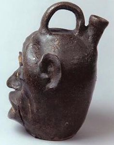 Stoneware glazed face jug attributed to the Edgefield District of South Carolina, about 1860-1880. Now in a private collection sold by David A. Schorsch at the 2002 Winter Antiques Show
