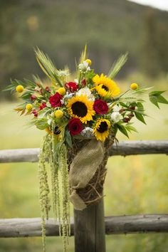 Possibly two tin buckets with burlap and lace at the bottom of the arch or at the entrance to the ceremony. With sunflowers, Delphinium, Iris etc.