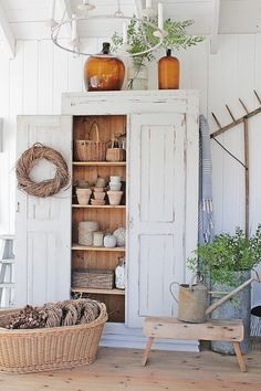 VIBEKE DESIGN Organized visible planting supplies & flower pots storage in tall armoire. Love clay pots