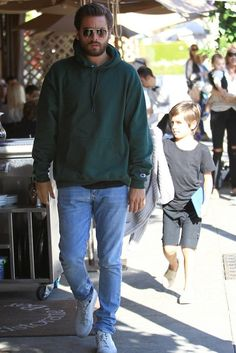 Scott Disick wearing Champion Reverse Weave Hoodie, Saint Laurent Aviator-Style Gold-Tone Sunglasses, Common Projects Achilles Low Sneakers, Saint Laurent Skinny-Fit Faded Washed-Denim Jeans