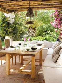 ChicDecó | Delightful dining/sitting area surrounded by a green lush garden. The space has been styled with a Moroccan inspired lantern, a rustic wooden table and a couple of woven chairs. On the beach, white and striped cushions in neutral-hues