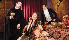 """I don't even know what is happening in this promo picture for Phantom: Las Vegas. Raoul's just giving the Phantom his best stink eye while trying to look fabulous with his hand on his thigh. The Phantom seems to be doing his best Bitch Please head toss and not to be outdone by Raoul, also has his foot on a chair. """"Look at my knee Christine. It is by far bigger than Raoul's."""" And Christine's sitting there with her apple against her face making eyes with the camera man."""