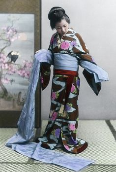 Hand-coloured photo of woman fastening her silk obi, ca. 1900-1920. S)
