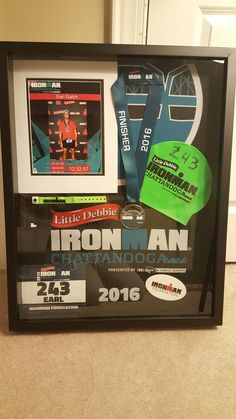 Ironman shadow box was homemade. Shadowbox from Hobby Lobby ($50 after coupon). Display your ironman, marathon or triathlon race medal, swim cap, race bib and other memorabilia. Simple, easy and way cheaper than having it professionally done. All you need is hot glue gun and a few pins and a vision. Make sure to keep lots of things from race day.
