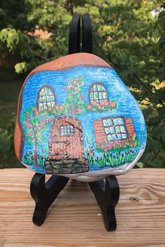 The Fairy Garden House Hand Painted Rock features a blue house with a door, windows, flower boxes, and flowers painted on the front and sides of a white background. The back of the stone shows the natural color and is signed by yours truly. Painted Rocks For Sale, Hand Painted Rocks, Gnome House, House On The Rock, Flower Boxes, Flowers, Fairy Garden Houses, Fireplace Mantle, Stone Art