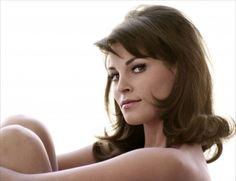 Raquel Welch, the 60s minx. Brunette with subtle curled flicks, midlength with short side swept fringe. Volume at crown.