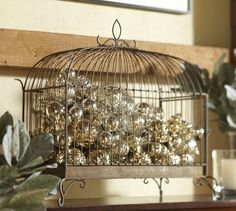 Christmas Ball Displayed In An Empty Bird Cage | The House of Beccaria holiday, bird cage, mercury glass, birdcag, wrought iron, christmas baubles, glass ornaments, christmas ornaments, pottery barn