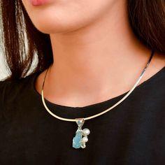 Pandantiv lucrat manual din argint, frumos ornamentat cu acvamarin nefinisat, topaz bleu fațetat, perle de cultură și calcedonia finisată caboșon.  Cod produs: DP255 Greutate: 7.44 gr. Lungime: 3.60 cm Lățime: 1.70 cm