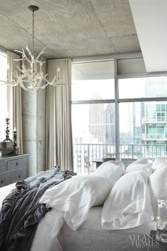 There is nothing more that I love at the end of the day than curling up with a good book in bed, with the chandelier dimmed, and looking out over my view of the city, says D'Ambrosio. The antler chandelier is vintage. Bed linens by Bella Notte.