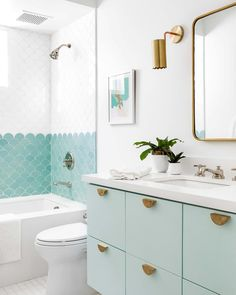 Aqua and white bathroom design. Mint green bathroom cabinet with turquoise and white scallop tile in shower. Brass accessories and pulls - love the scallop trim on that sconce! Mint Bathroom, Bathroom Kids, Bathroom Renos, Turquoise Bathroom, Master Bathroom, Girl Bathrooms, Mint Green Bathrooms, Bathroom Colors, Tiled Walls In Bathroom