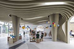 Undulating ribbed ceilings made of plywood add a sense of play to the interiors. #dwell #designnews #vietname #kindergarten Window Frame Colours, Activity Based Learning, Circular Buildings, Education And Development, Wooden Architecture, Shaped Windows, Outdoor Playground, Learning Spaces, Learning Environments