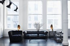 Interior of a living room with black chesterfield sofas