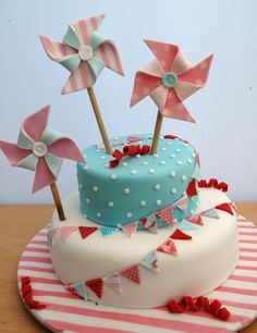 I wanted a more grown up yet girly cake for my 9 year old with a carnival/party theme. The dark colour looks red on the photos but was actually a deep pink. I loved doing the pinwheels - thanks to the people on CC that have posted bunting & pinwheel cakes for the inspiration