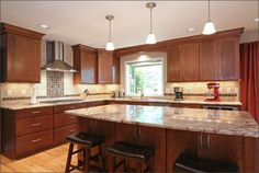 Love this beautiful kitchen remodel with wood cabinets and granite countertops, plus pendant lights