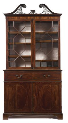 A Fine George III mahogany & satinwood secrétaire bookcase, possibly by Thomas Chippendale, Circa 1775, the upper section fitted with a pair of glazed doors with geometric glazing bars & surmounted by a pierced fret-carved swan-neck broken pediment ending in fluted & beaded roundels, the projecting lower section fitted with a secretaire drawer opening to satinwood-veneered small drawers & pigeon holes above a pair of cupboard doors. H 8 ft 2 in.; 4 ft. 4 in.; D 25 in.