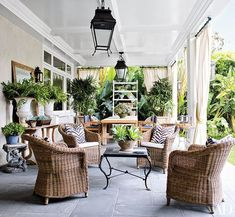 On the main terrace of fashion executives Patrick Wade and Dave DeMattei's home in Beverly Hills, California, wicker club chairs are arranged around a vintage French Art Deco iron table | archdigest.com