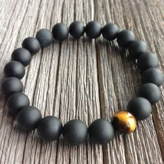 Mens matte onyx beaded bracelet accented with a single tigers eye bead. 10mm bead bracelet shown in pictures 1 to 3. 8mm option shown in picture 4  Good to know: Onyx is a stone of centering, self-control and intuitive guidance. While tigers eye promotes optimism, psychic ability and intuition. It also stimulates awareness and understanding and has been used to attract and maintain wealth.  Features  ~ Grade AA 10mm or 8mm matte onyx beads ~ Grade A 10mm or 8mm single tigers eye bead…