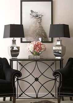 A lovely, detailed console table is placed between two black chairs with silver nailhead trim that matches the twin silver lamps with black shades. A lovely, symmetrical vignette....V